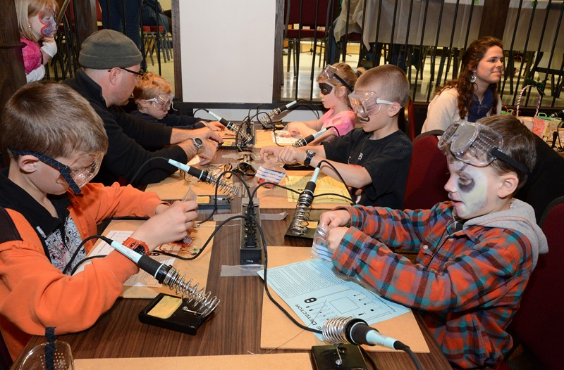 Kids soldering electronic kits at Madlab workshop