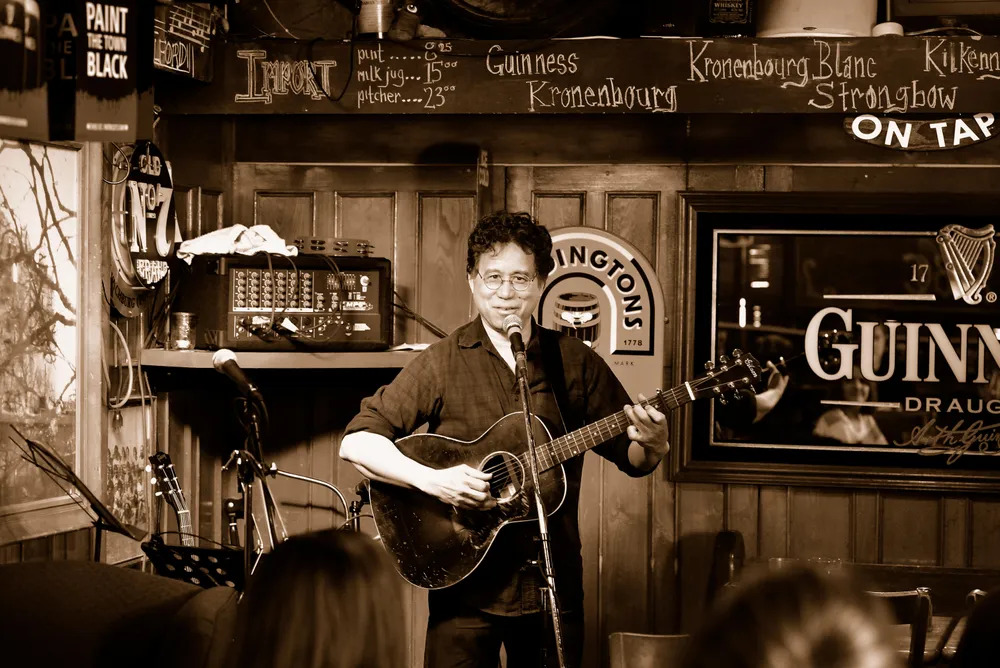 Photo of Vince Halfhide playing his guitar at a microphone, in the corner of a bar