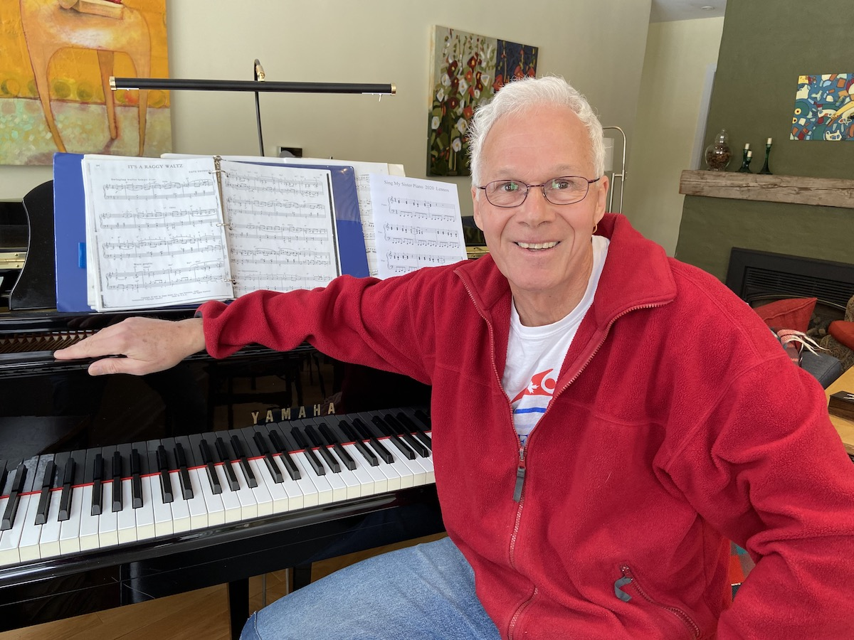Photo of Andy Rush sitting in front of his piano
