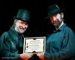 Hollis Morgan (left), presents Dean Verger (right) with a lifetime membership to Spirit of Rasputin's Arts Society