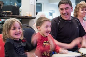 A Dad with his two young kids having an amazing time in the drumming circle workshop at OGF 2013.  Photographer: Michelle Tardiff
