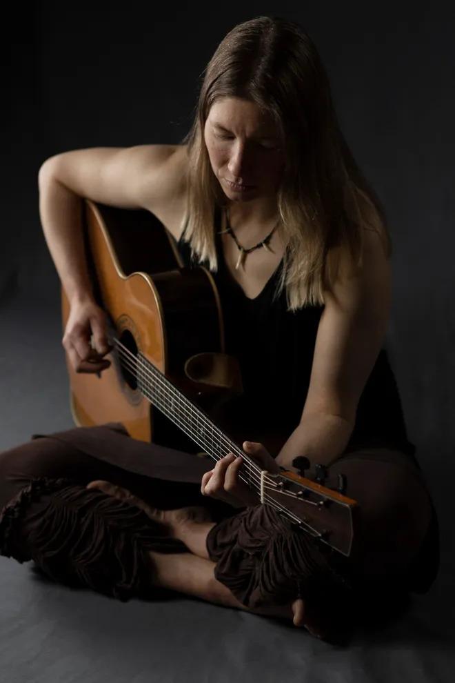 Photo of Kate Weekes seated cross-legged playing guitar