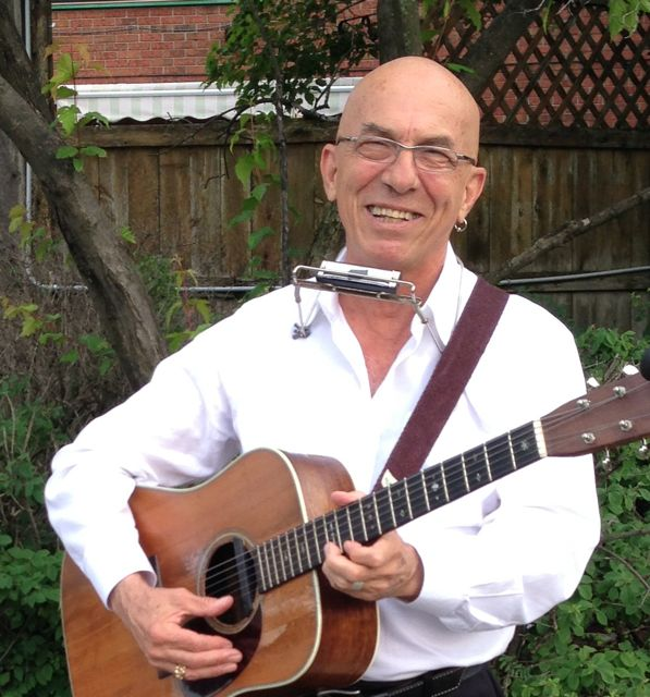 Photo of Sneezy Waters smiling, holding a guitar and with a harmonica holder around his neck.